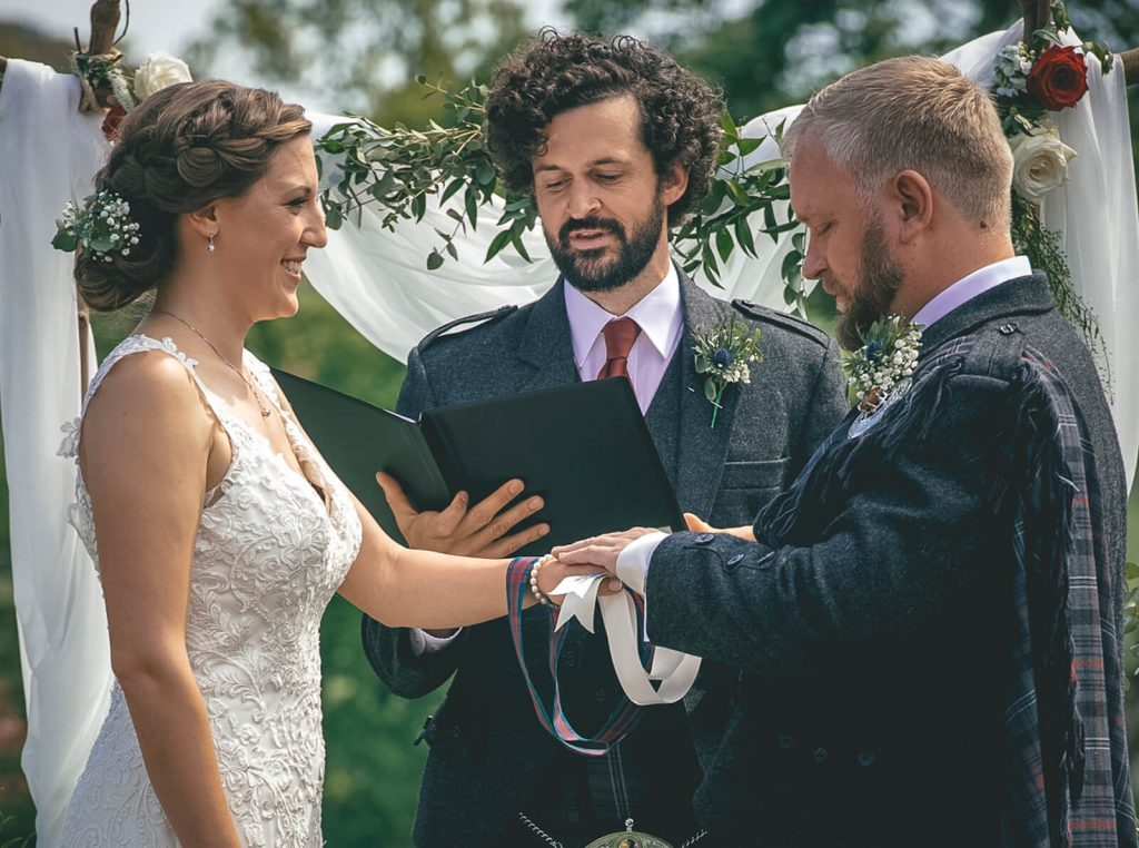 photo of a couple and a celebrant doing a hand-fasting symbolic ritual at a wedding
