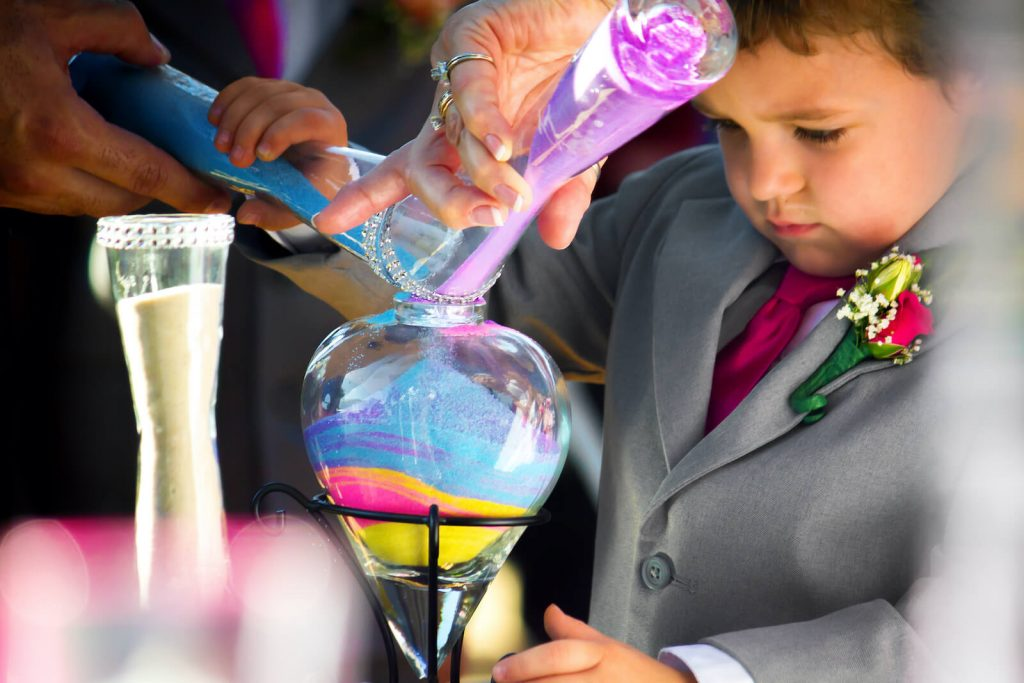 photo of a young boy pouring coloured sand into a vase used for a symbolic ritual sand ceremony with the celebrant angel