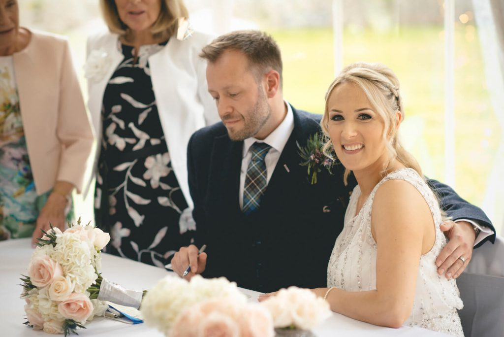 couple signing the register at the civil ceremony celebrant led wedding with the celebrant angel