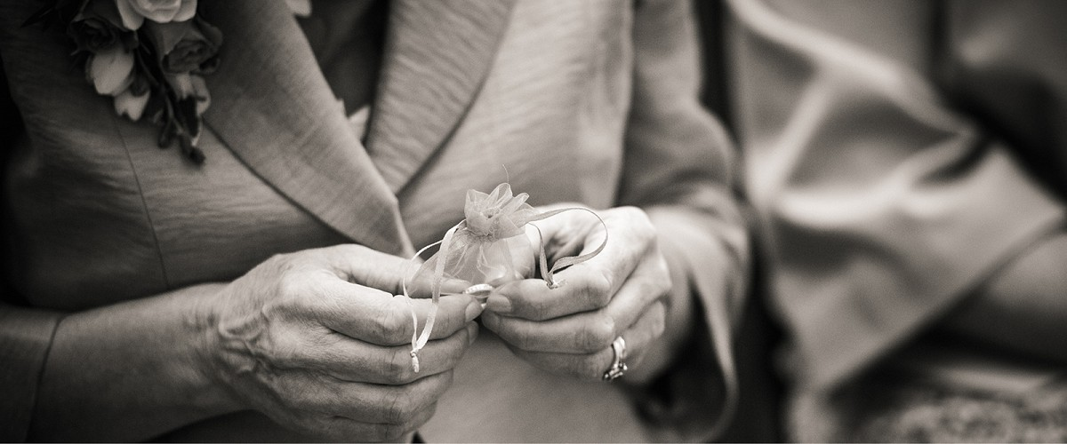 photo of 2 hands holding a bag with 2 wedding rings in for a symbolic ritualring warming symbolic action ceremony with the celebrant angel