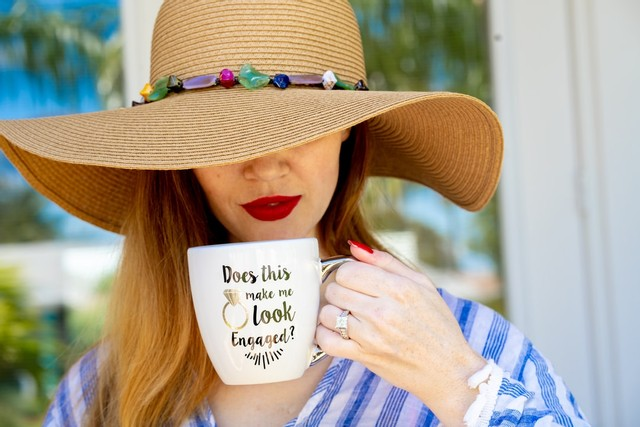 lady with a hat on and a mug what to do after you get engaged