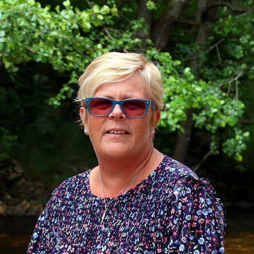 Mary Gibson, the celebrant angel aberdeen sitting by the river wearing sunglasses