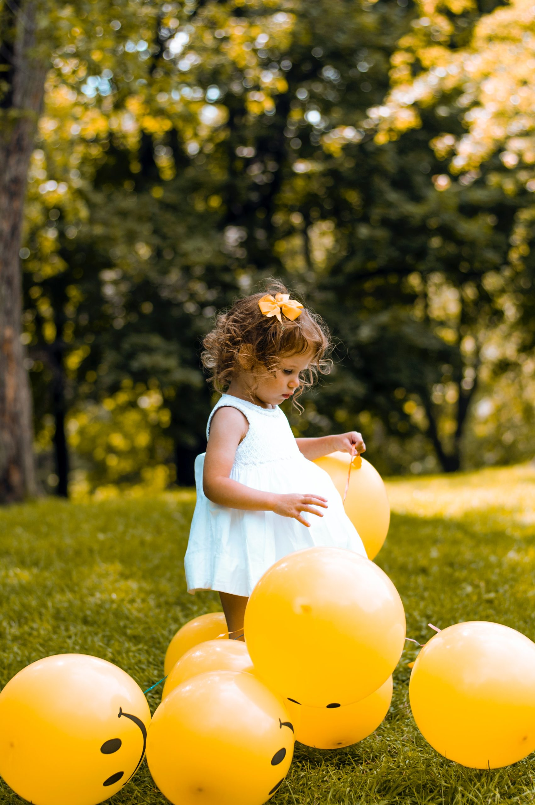 a photo of a little girl in a white dress playing in a meadow with yellow ballons