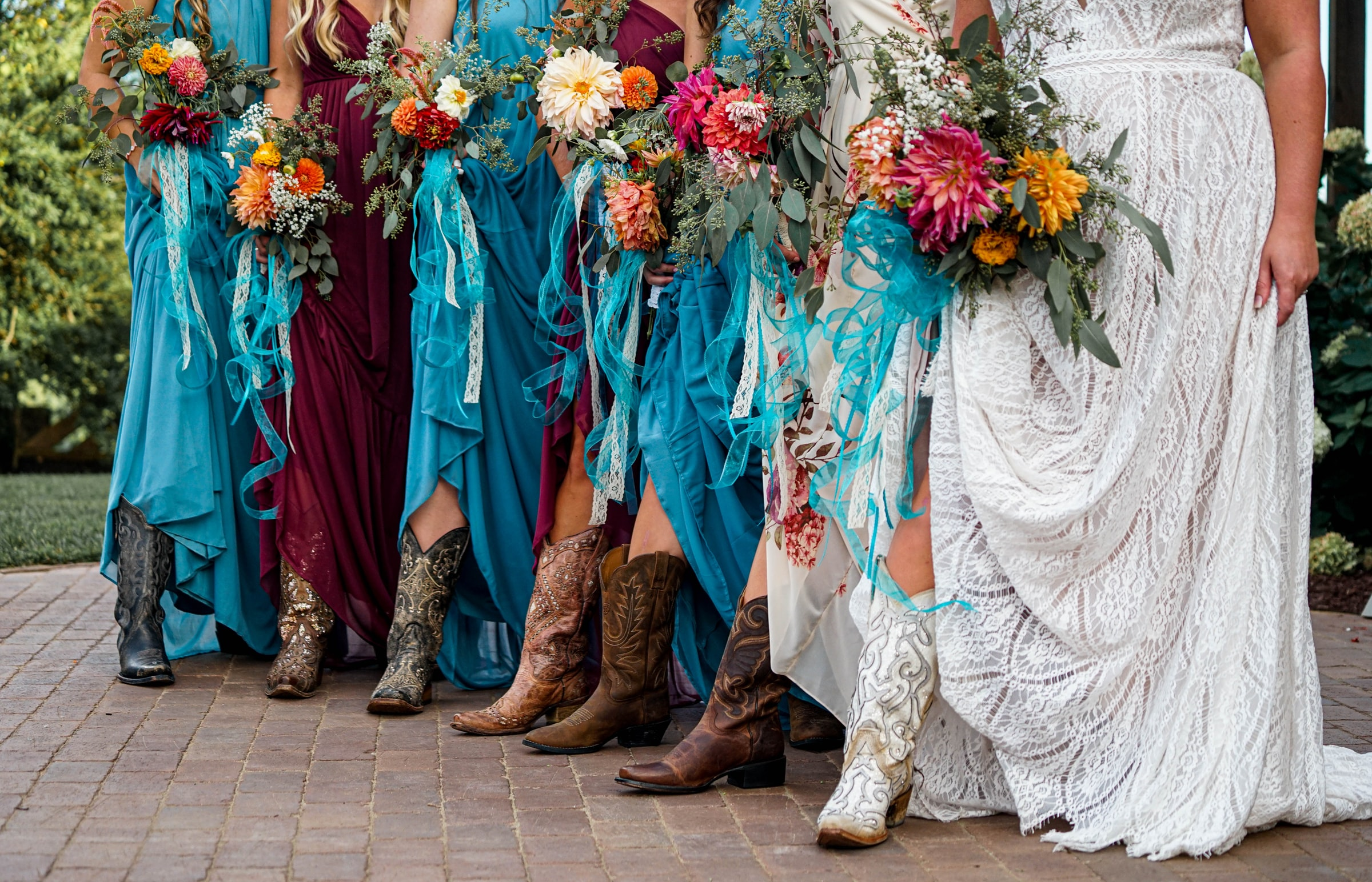 brides maids all dressed in long dresses with cowboy boots on
