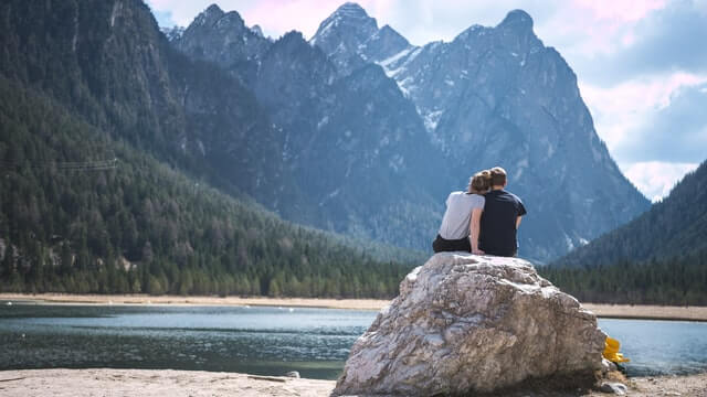 couple sitting on a rock on a loch planning to propose