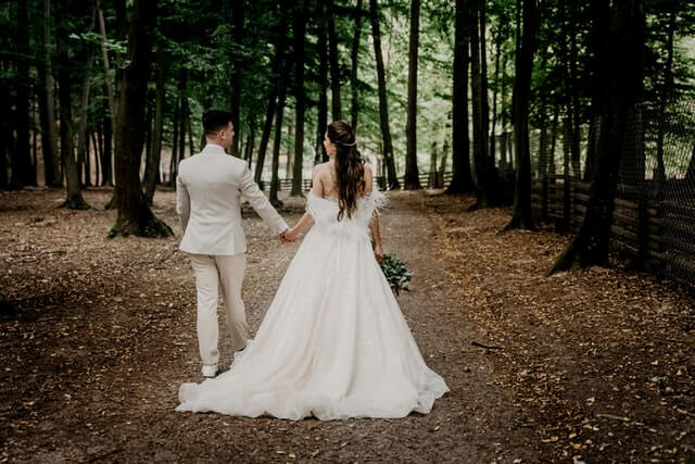 couple walking down the aisle in a forest setting