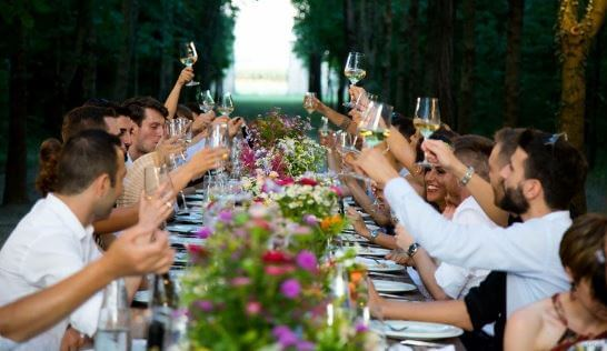 a large long table filled with people and flowers at a wedding ceremony