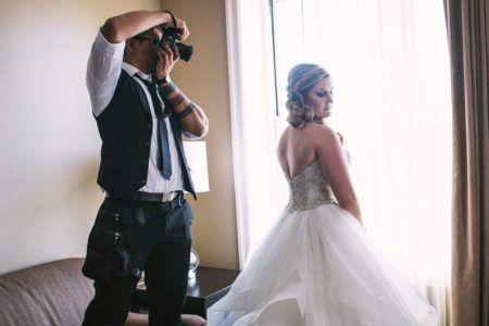 wedding photographier taking photo for bride at window how to choose a wedding photographer