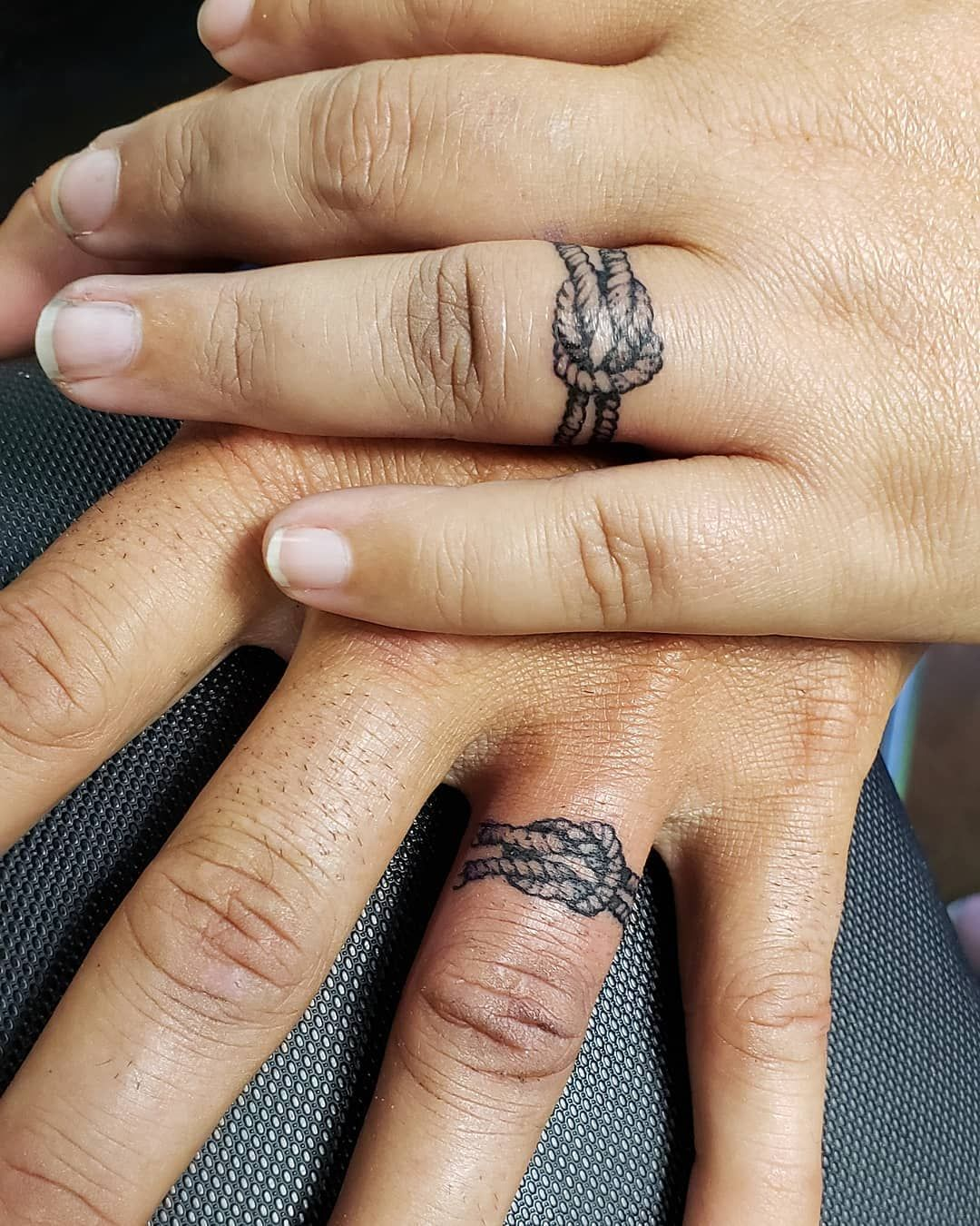 photo of a couples hands on top of each other showing off a wedding ring tattoo
