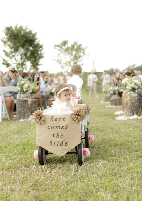 2 young children on a wedding aisle, one pulling the other in a cart