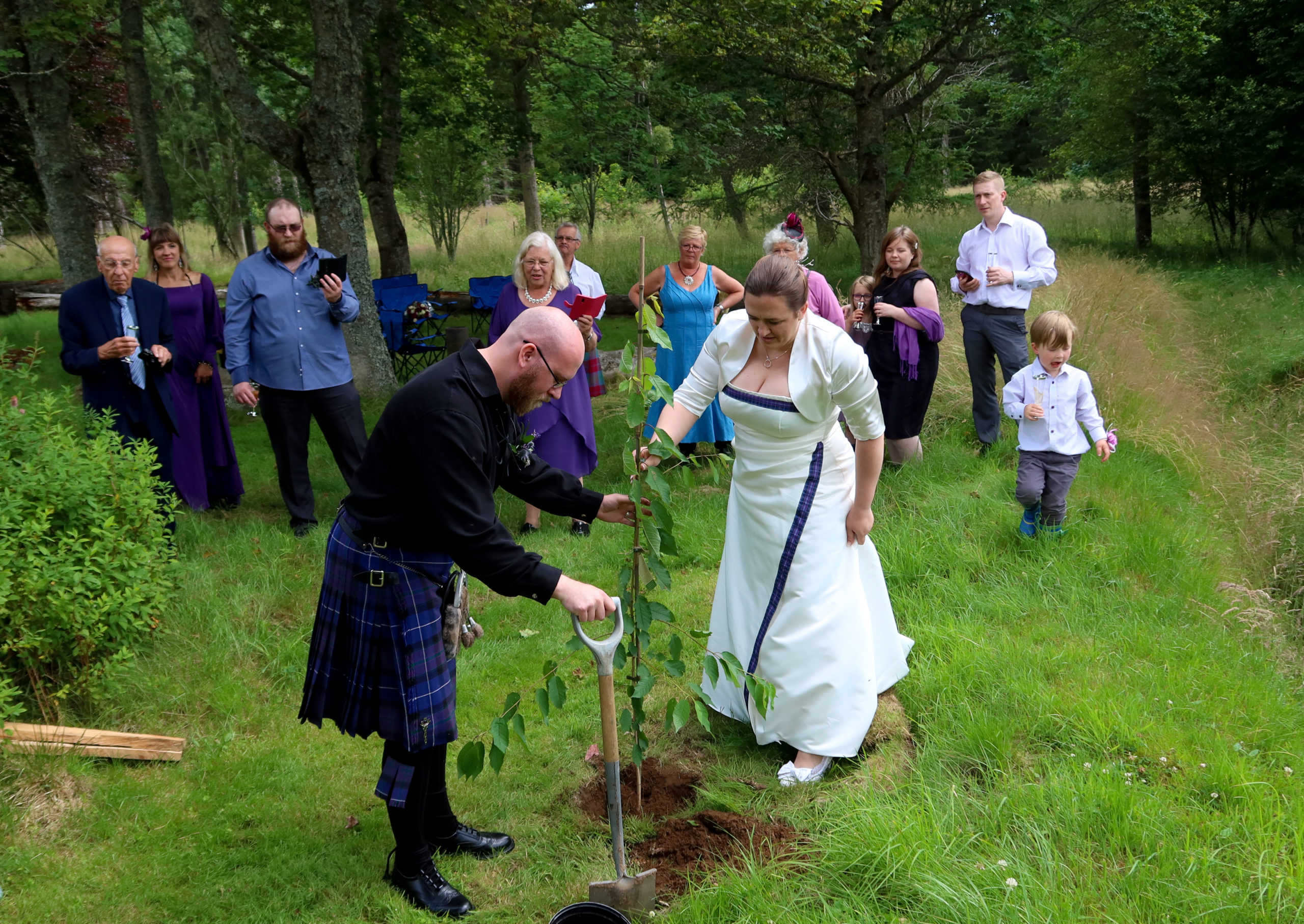 couple planting a tree in their wedding ceremony with friends