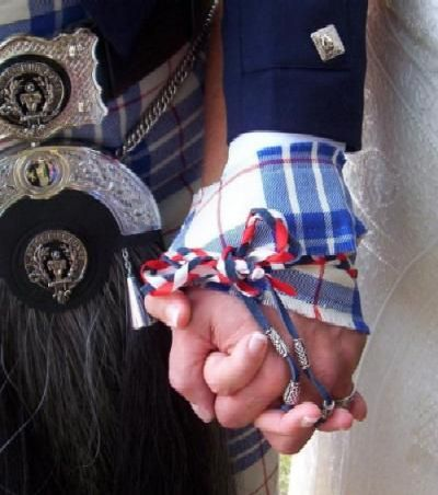 a handfasting tie round a couples hands