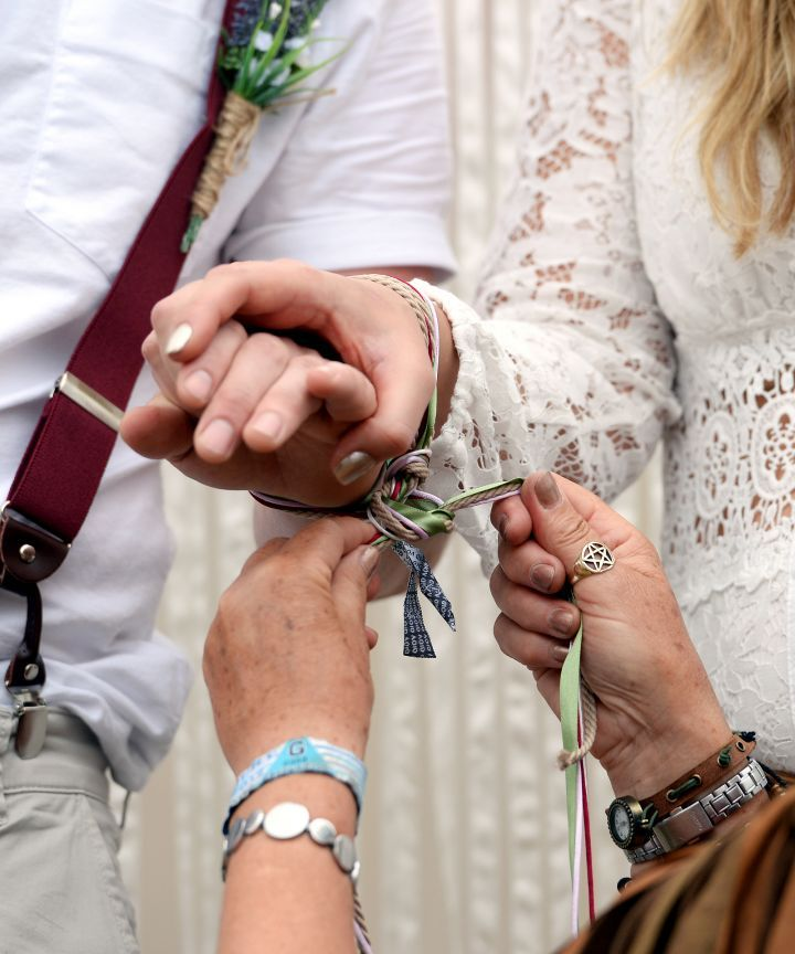 Photo of a couple doing a handfasting ceremony at their wedding