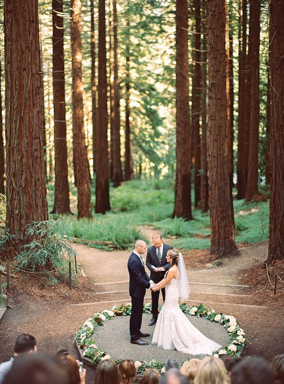 couple standing in a forest getting married in an outdoor ceremony