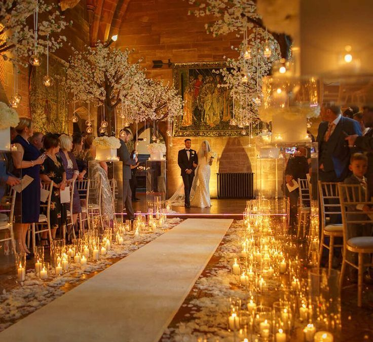 wedding aisle covered in candles with couple walking down the aisle in how to choose a wedding venue aberdeen