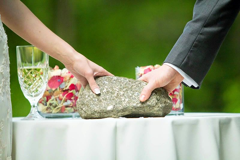 two hands holding a stone on a wedding table the oathing stone ceremony with mary gibson aberdeen