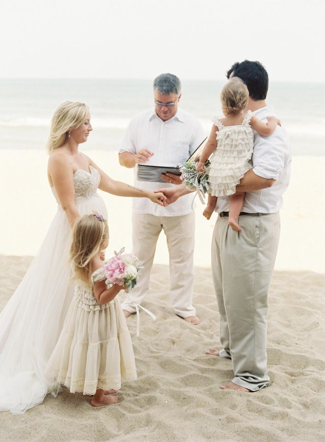couple and their children on a beach doing a vow renewal ceremony