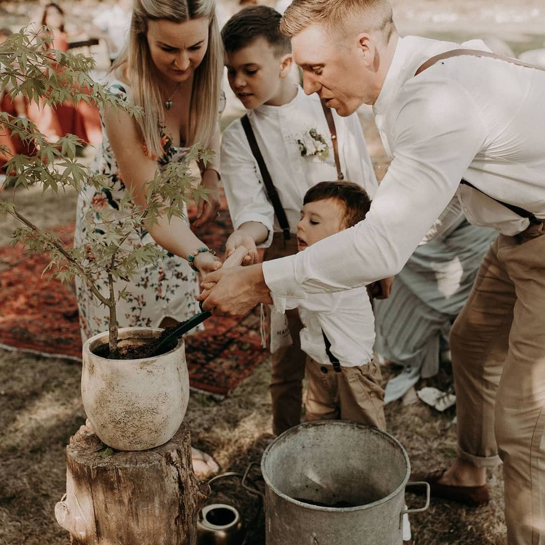 A photo of a family planting a tree as a symbolic ritual at wedding ceremony with the celebrant angel