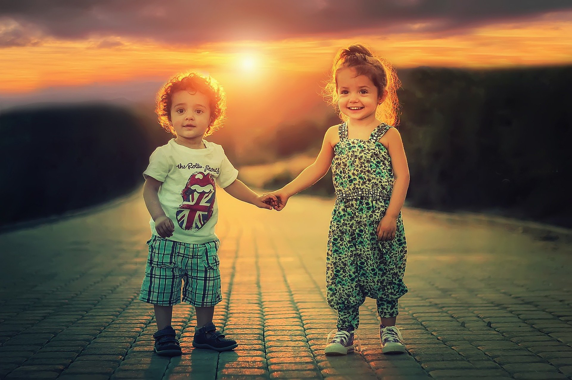 2 children holding hands in the sunset