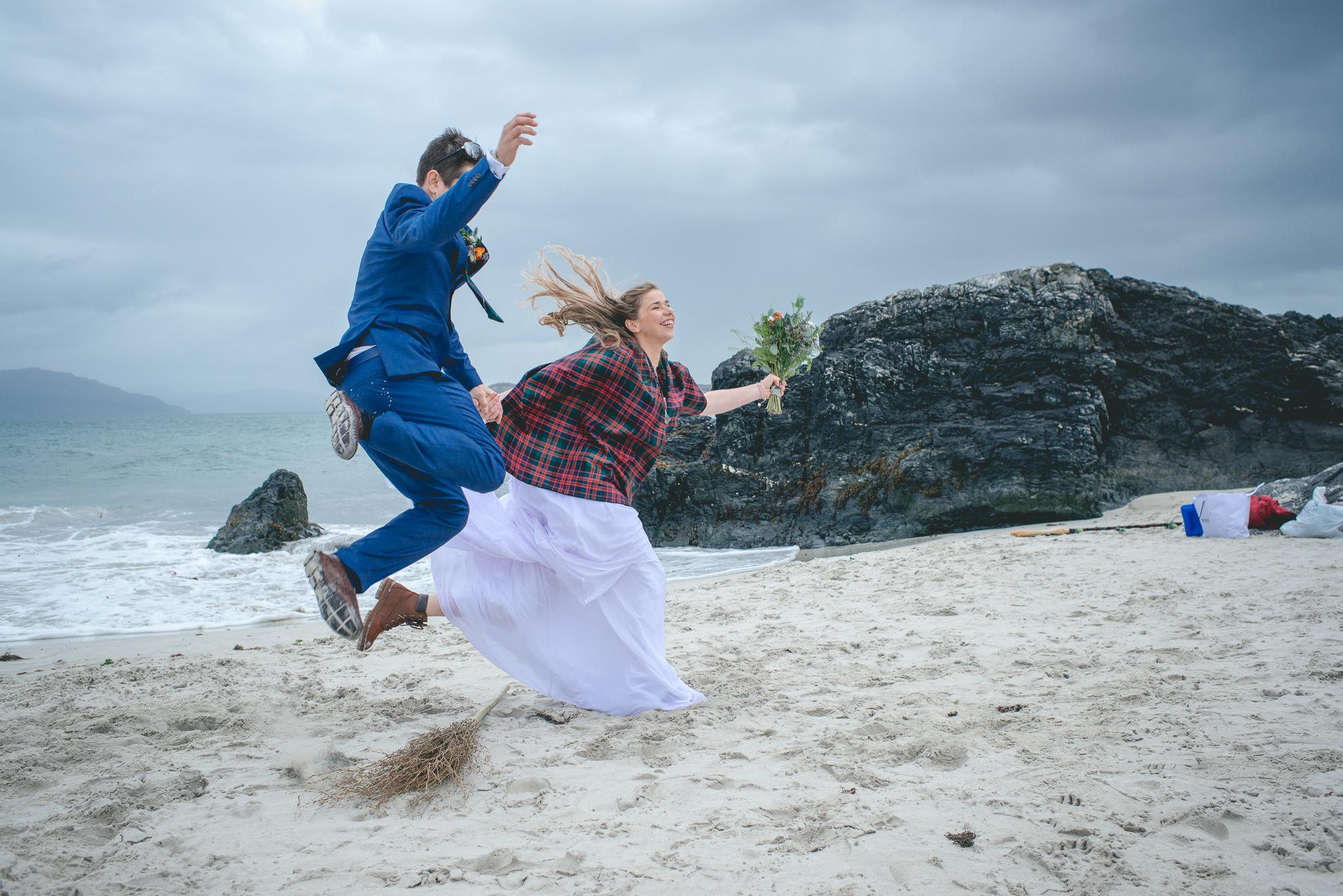 couple jumping the broom on an beach