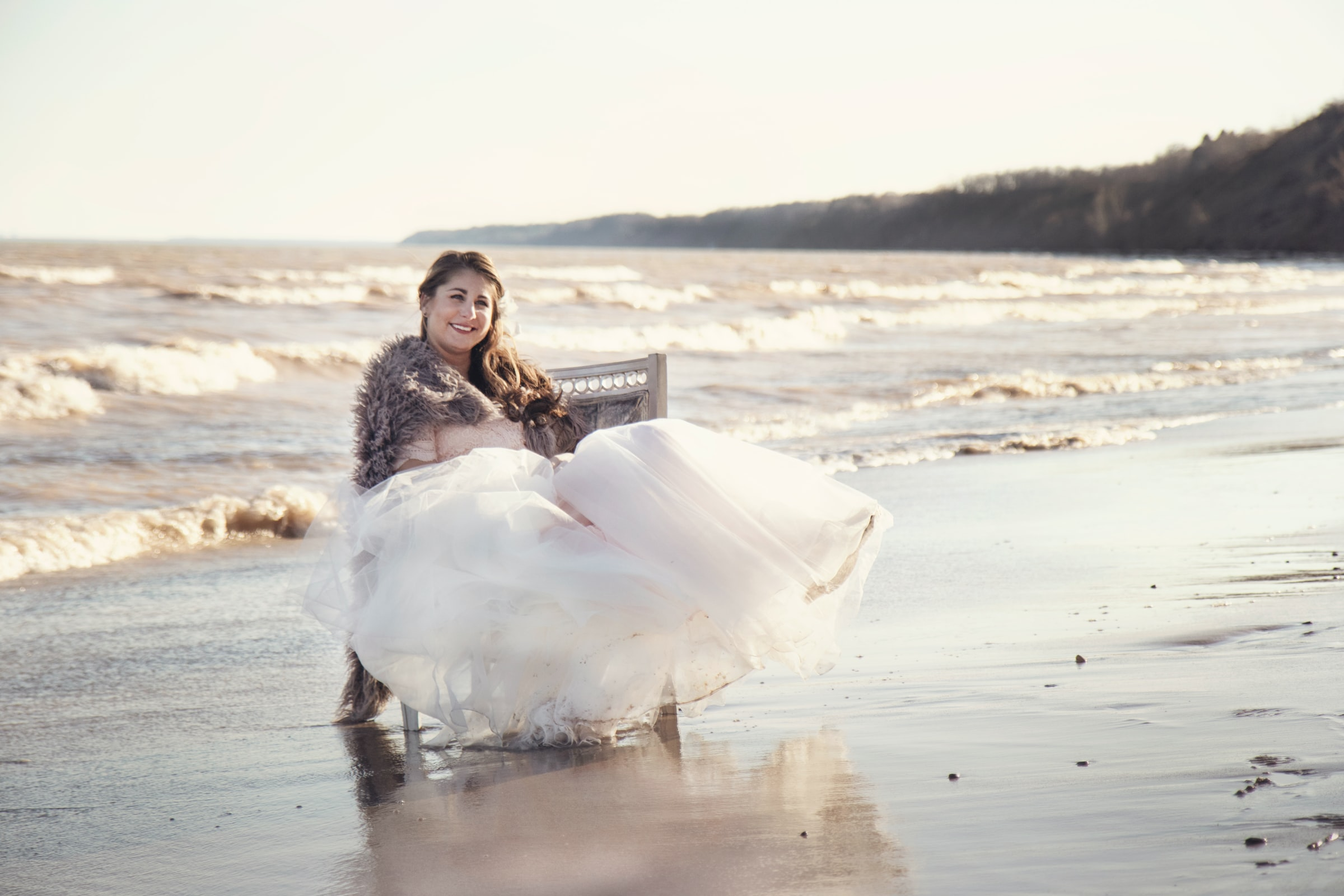 bride sitting on a seat at the edge of the sea for an outdoor wedding