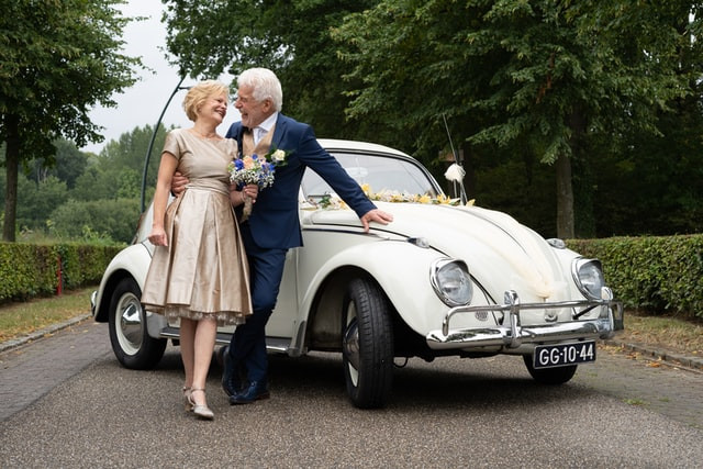 photo of couple standing beside a car during a commitment ceremony