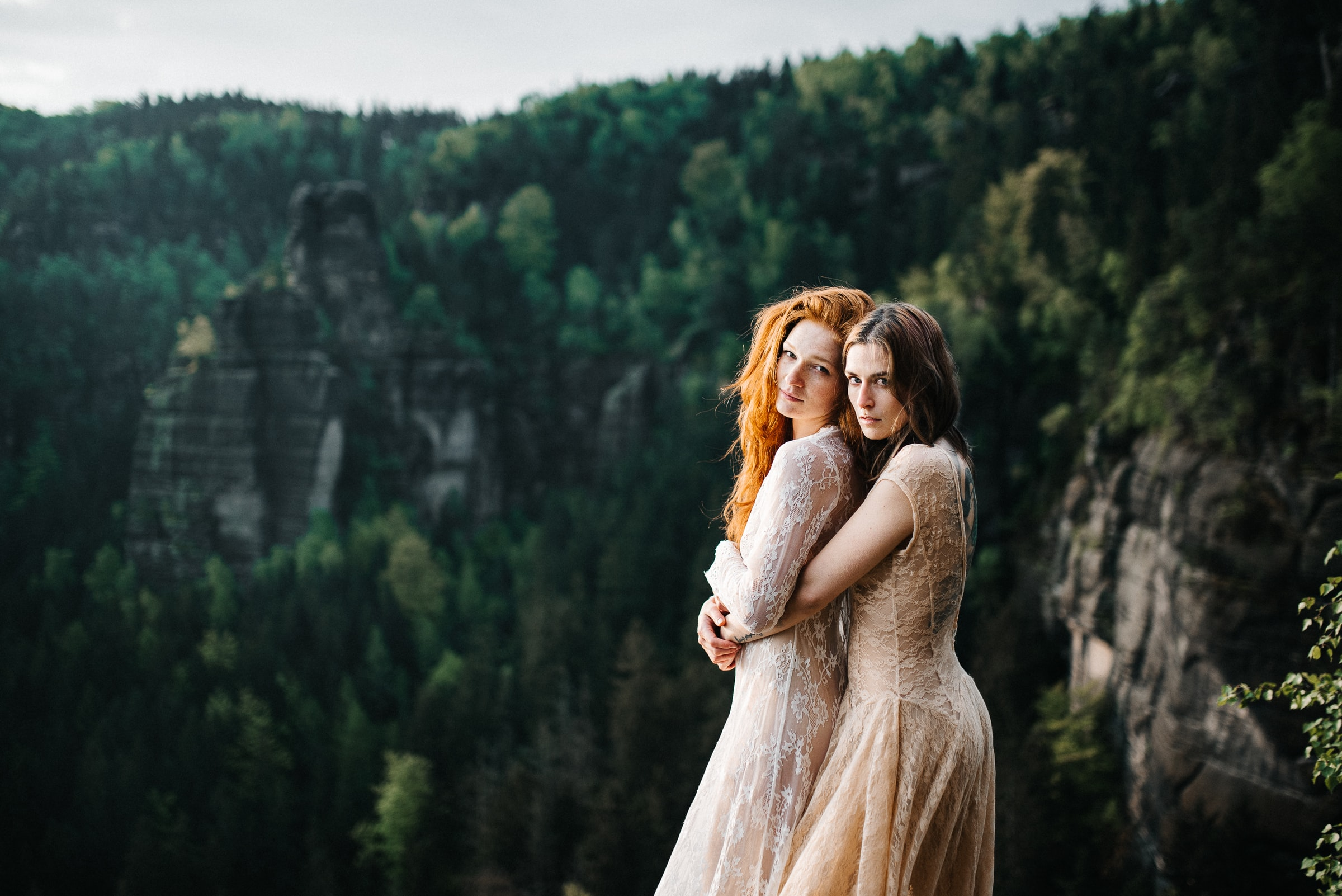 2 young ladies hugging in wedding dresses on a cliff top couples ceremonies with the celebrant angel in aberdeen