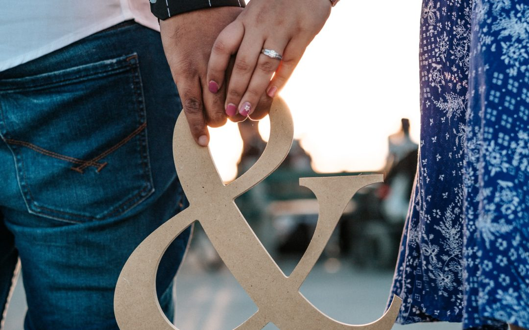 planning a proposal couple hand in hand carrying a and sign