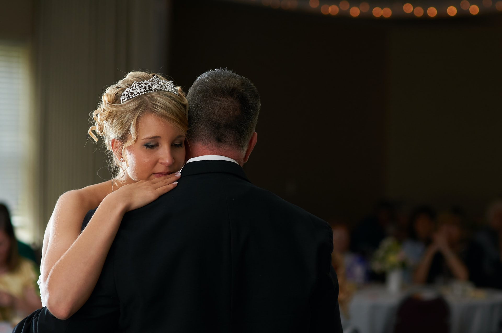 bride with her head on partners shoulder crying, how to calm wedding day nerves