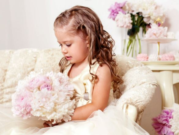 picture of a flower girl sitting holding a posey type of wedding bouquet with the celebrant angel